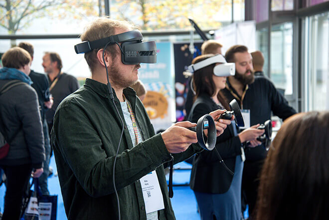 Man going through a VR demo, standing with a headset on, surrounded by other people trying and some other facilitating the demo.